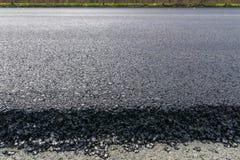 Πρόσφατα τοποθετημένη μαύρη άσφαλτος πίσσας με μια υψηλή άκρη στο αμμοχάλικο Στοκ Εικόνες