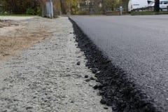 Πρόσφατα τοποθετημένη μαύρη άσφαλτος πίσσας με μια υψηλή άκρη στο αμμοχάλικο Στοκ Εικόνα
