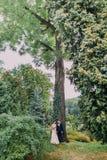 Πρόσφατα το ζεύγος κάτω από το υψηλό ακακία-δέντρο με τον κισσό Ακριβώς παντρεμένο περπάτημα στο πάρκο στην ημέρα του γάμου τους Στοκ φωτογραφία με δικαίωμα ελεύθερης χρήσης
