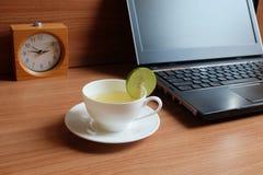 Πρόσφατα χυμός ασβέστη σε ένα άσπρο φλυτζάνι, και lap-top στοκ εικόνα