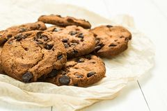 Πρόσφατα ψημένα σπιτικά μπισκότα σοκολάτας σε χαρτί περγαμηνής με έναν άσπρο ξύλινο πίνακα στοκ εικόνες