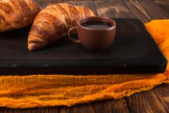Πρόσφατα ψημένη croissant μαρμελάδα, φλιτζάνι του καφέ στο άσπρο φλυτζάνι στο καφετί ξύλινο υπόβαθρο Γαλλικές φρέσκες ζύμες προγε Στοκ φωτογραφία με δικαίωμα ελεύθερης χρήσης
