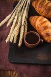 Πρόσφατα ψημένη croissant μαρμελάδα, φλιτζάνι του καφέ στο άσπρο φλυτζάνι στο καφετί ξύλινο υπόβαθρο Γαλλικές φρέσκες ζύμες προγε Στοκ εικόνα με δικαίωμα ελεύθερης χρήσης