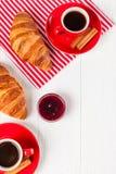 Πρόσφατα ψημένος croissant στην πετσέτα, φλιτζάνι του καφέ στο κόκκινο φλυτζάνι στο άσπρο ξύλινο υπόβαθρο Γαλλικές φρέσκες ζύμες  Στοκ Εικόνα