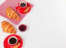 Πρόσφατα ψημένος croissant στην πετσέτα, φλιτζάνι του καφέ στο κόκκινο φλυτζάνι στο άσπρο ξύλινο υπόβαθρο Γαλλικές φρέσκες ζύμες  Στοκ φωτογραφίες με δικαίωμα ελεύθερης χρήσης