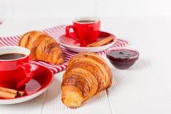 Πρόσφατα ψημένος croissant στην πετσέτα, φλιτζάνι του καφέ στο κόκκινο φλυτζάνι στο άσπρο ξύλινο υπόβαθρο Γαλλικές φρέσκες ζύμες  Στοκ Φωτογραφία