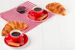 Πρόσφατα ψημένος croissant στην πετσέτα, φλιτζάνι του καφέ στο κόκκινο φλυτζάνι στο άσπρο ξύλινο υπόβαθρο Γαλλικές φρέσκες ζύμες  Στοκ εικόνες με δικαίωμα ελεύθερης χρήσης