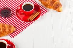 Πρόσφατα ψημένος croissant στην πετσέτα, φλιτζάνι του καφέ στο κόκκινο φλυτζάνι στο άσπρο ξύλινο υπόβαθρο Γαλλικές φρέσκες ζύμες  Στοκ φωτογραφία με δικαίωμα ελεύθερης χρήσης