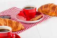 Πρόσφατα ψημένος croissant στην πετσέτα, φλιτζάνι του καφέ στο κόκκινο φλυτζάνι στο άσπρο ξύλινο υπόβαθρο Γαλλικές φρέσκες ζύμες  Στοκ Εικόνες