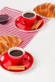 Πρόσφατα ψημένος croissant στην πετσέτα, φλιτζάνι του καφέ στο κόκκινο φλυτζάνι στο άσπρο ξύλινο υπόβαθρο Γαλλικές φρέσκες ζύμες  Στοκ Φωτογραφίες