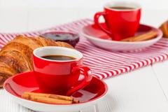 Πρόσφατα ψημένος croissant στην πετσέτα, φλιτζάνι του καφέ στο κόκκινο φλυτζάνι στο άσπρο ξύλινο υπόβαθρο Γαλλικές φρέσκες ζύμες  Στοκ εικόνα με δικαίωμα ελεύθερης χρήσης