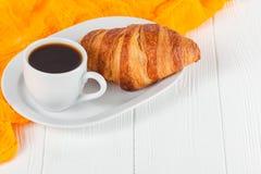 Πρόσφατα ψημένος croissant χυμός από πορτοκάλι, μαρμελάδα, φλυτζάνι του μαύρου καφέ στο άσπρο ξύλινο υπόβαθρο Γαλλικές φρέσκες ζύ στοκ εικόνες