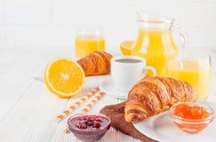 Πρόσφατα ψημένος croissant, χυμός από πορτοκάλι, νωποί καρποί, μαρμελάδα στο άσπρο ξύλινο υπόβαθρο Γαλλικές φρέσκες ζύμες προγευμ Στοκ εικόνα με δικαίωμα ελεύθερης χρήσης