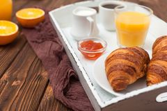 Πρόσφατα ψημένος croissant, χυμός από πορτοκάλι, νωποί καρποί, μαρμελάδα στο καφετί ξύλινο υπόβαθρο Γαλλικές φρέσκες ζύμες προγευ Στοκ Φωτογραφία