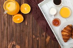 Πρόσφατα ψημένος croissant, χυμός από πορτοκάλι, νωποί καρποί, μαρμελάδα στο καφετί ξύλινο υπόβαθρο Γαλλικές φρέσκες ζύμες προγευ Στοκ Εικόνα