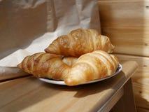 Πρόσφατα ψημένος croissants σε ένα μικρό άσπρο πιάτο r στοκ εικόνα
