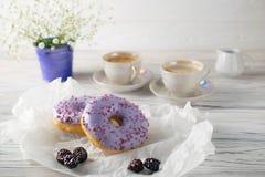Πρόσφατα ψημένο βατόμουρο donuts με τον καφέ και την κρέμα, ρύθμιση προγευμάτων πρωινού στοκ φωτογραφία