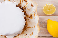 Πρόσφατα ψημένο κέικ λεμονιών με την άσπρη τήξη και τα φρέσκα λεμόνια Στοκ εικόνες με δικαίωμα ελεύθερης χρήσης