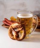 Πρόσφατα ψημένο σπιτικό μαλακό pretzel με το άλας στον άσπρο πίνακα με το ποτήρι της μπύρας Στοκ Εικόνες