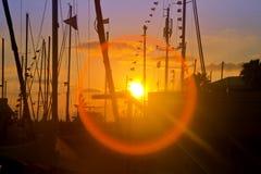 Πρόσφατο ηλιοβασίλεμα στη μαρίνα με τις σκιαγραφίες και την επίδραση φλογών Στοκ φωτογραφίες με δικαίωμα ελεύθερης χρήσης