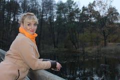 Πρόσφατο φθινόπωρο στη δασική, δασική λίμνη, ξανθό κορίτσι παλτών από τη λίμνη Στοκ Εικόνες