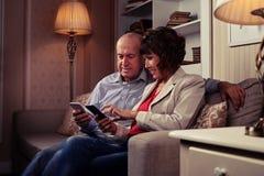 Πρόσχαρο ζεύγος που εξετάζει τα τηλέφωνα Στοκ Εικόνα