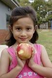 Πρόσωπα χαμόγελου ενός παιδιού και της Apple της. Στοκ Φωτογραφία