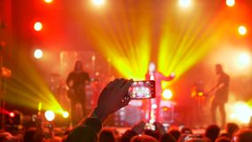 Πρόσωπο ανεμιστήρων που παίρνει το βίντεο και τις φωτογραφίες στο κινητό smartphone στο κόμμα συναυλίας στο φωτισμό επικέντρων απόθεμα βίντεο