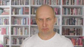 Πρόσωπο ατόμων πορτρέτου που εξετάζει τη κάμερα στο υπόβαθρο βιβλιοθηκών απόθεμα βίντεο