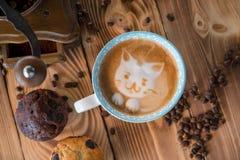 Πρόσωπο αφρού γατών του καφέ τέχνης latte στο φλυτζάνι με τα διεσπαρμένα φασόλια και τα μπισκότα καφέ στον παλαιό ξύλινο πίνακα Στοκ Εικόνα