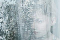 Πρόσωπο γυναικών πίσω από το διαφανές ύφασμα Στοκ εικόνες με δικαίωμα ελεύθερης χρήσης