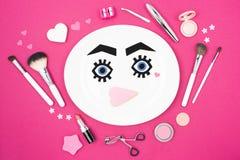 Πρόσωπο εγγράφου στο πιάτο τις βούρτσες makeup και τα προϊόντα ομορφιάς που απομονώνονται με στο ροζ Στοκ φωτογραφίες με δικαίωμα ελεύθερης χρήσης