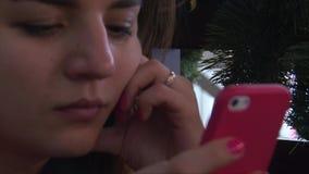 Πρόσωπο και χέρια κοριτσιών κινηματογραφήσεων σε πρώτο πλάνο που δακτυλογραφούν στο smartphone φιλμ μικρού μήκους