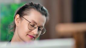 Πρόσωπο κινηματογραφήσεων σε πρώτο πλάνο της αρκετά ενθουσιώδους νέας γυναίκας ζωγράφος στα γυαλιά που απολαμβάνει την εικόνα σχε απόθεμα βίντεο