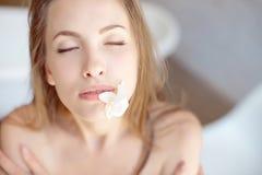 Πρόσωπο κινηματογραφήσεων σε πρώτο πλάνο της όμορφης νέας γυναίκας με το δέρμα υγείας και του λουλουδιού στο στόμα στοκ εικόνες