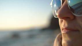 Πρόσωπο κινηματογραφήσεων σε πρώτο πλάνο του όμορφου κοριτσιού στα γυαλιά ηλίου Παλιρροιακός άντεξε την αντανάκλαση απόθεμα βίντεο