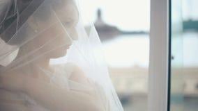 Πρόσωπο κινηματογραφήσεων σε πρώτο πλάνο της πανέμορφης στοχαστικής ξανθής νύφης που καλύπτεται στο διαφανές πέπλο που προσέχει τ φιλμ μικρού μήκους