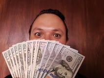 πρόσωπο με την έκφραση συγκίνησης ενός νεαρού άνδρα και αμερικανικών τραπεζογραμματίων στοκ φωτογραφίες