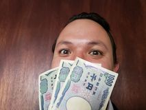 πρόσωπο με την έκφραση συγκίνησης ενός νεαρού άνδρα και ιαπωνικών τραπεζογραμματίων στοκ εικόνα με δικαίωμα ελεύθερης χρήσης