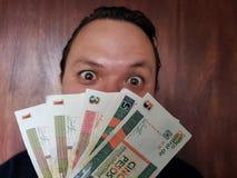 πρόσωπο με την έκφραση συγκίνησης ενός νεαρού άνδρα και κουβανικών τραπεζογραμματίων στοκ φωτογραφίες