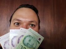 πρόσωπο με την έκφραση συγκίνησης ενός νεαρού άνδρα και σιγκαπούριος τραπεζογραμματίων στοκ εικόνες