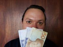 πρόσωπο με την έκφραση συγκίνησης ενός νεαρού άνδρα και σουηδικών τραπεζογραμματίων στοκ φωτογραφία με δικαίωμα ελεύθερης χρήσης
