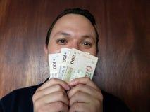 πρόσωπο με την έκφραση συγκίνησης των τραπεζογραμματίων Ουρουγουανών νεαρών άνδρων και εκμετάλλευσης στοκ φωτογραφίες
