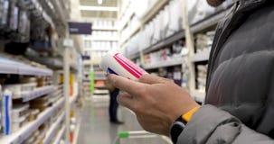 Πρόσωπο με τη στεγανωτική ουσία στο κατάστημα υλικού απόθεμα βίντεο