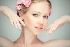 Πρόσωπο ομορφιάς της νέας όμορφης γυναίκας με τα ρόδινα λουλούδια Στοκ εικόνες με δικαίωμα ελεύθερης χρήσης