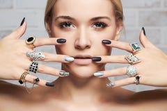 Πρόσωπο ομορφιάς Χέρια γυναικών ` s με τα δαχτυλίδια κοσμήματος Στοκ Εικόνες