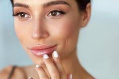 Πρόσωπο ομορφιάς Όμορφη γυναίκα σχετικά με τα χείλια με το χειλικό βάλσαμο επάνω στοκ φωτογραφία