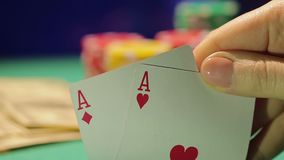 Πρόσωπο που απολαμβάνει το επιτυχές παιχνίδι πόκερ με το ζευγάρι των άσσων, στοιχηματίζοντας τα μετρητά και τα τσιπ φιλμ μικρού μήκους