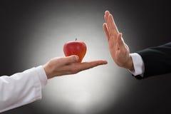 Πρόσωπο που αρνείται το μήλο που κατέχει ο γιατρός Στοκ Φωτογραφίες