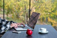 Πρόσωπο που εργάζεται στον υπολογιστή με την κούπα τηλεφωνικού καφέ στο μαύρο ξύλινο πίνακα στοκ φωτογραφίες με δικαίωμα ελεύθερης χρήσης